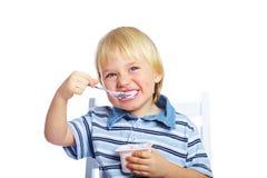 pojke som äter little yoghurt royaltyfria foton