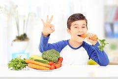Pojke som äter moroten och gör en gest lycka som placeras på tabellen royaltyfri foto