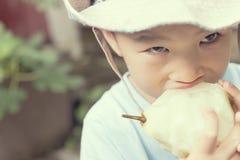 Pojke som äter päronet Arkivfoto