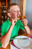 Pojke som äter pizza Royaltyfri Foto