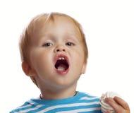 Pojke som äter sötsakerna Arkivbild