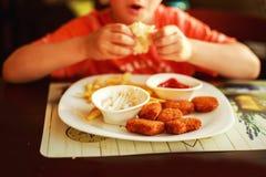 Pojke som äter snabbmat barnet som äter fransmansmåfiskar med klumpar Arkivfoto