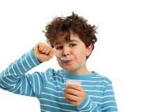 pojke som äter yoghurt Arkivfoto