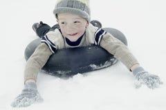 Pojke som åka släde på snöröret Arkivfoto