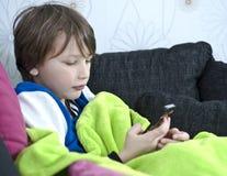 Pojke som överför textmeddelandet Arkivfoton