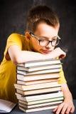 Pojke som överst tar en vila av böcker royaltyfri bild