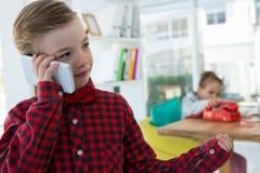 Pojke som affärsledaren som talar på mobilephonen Arkivfoton