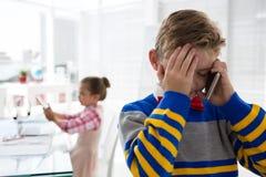 Pojke som affärsledaren som talar på mobiltelefonen Fotografering för Bildbyråer