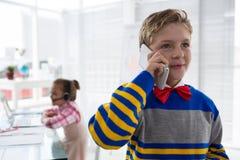 Pojke som affärsledaren som talar på mobiltelefonen Arkivfoton