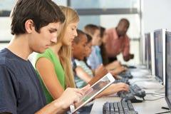 Pojke som använder den Digital minnestavlan i datorgrupp Arkivbilder