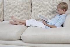 Pojke som använder den Digital minnestavlan på soffan Royaltyfria Bilder