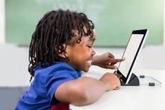 Pojke som använder den digitala minnestavlan i klassrum royaltyfria foton