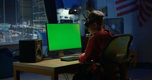 Pojke som använder en dator, medan bära VR-hörlurar med mikrofon stock video