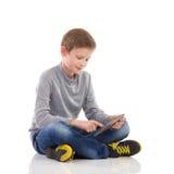 Pojke som använder en digital minnestavla Royaltyfri Bild