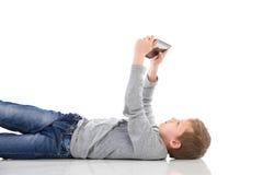 Pojke som använder en minnestavla. Arkivbild