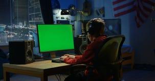 Pojke som använder hans dator på natten arkivfilmer