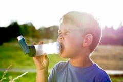 Pojke som använder inhalatorn för astma i natur Royaltyfri Foto