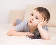 Pojke som använder minnestavlan Arkivbilder