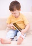 Pojke som använder minnestavlan Arkivfoton