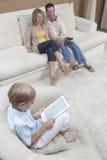 Pojke som använder den Digital minnestavlan med föräldrar som håller ögonen på TV Royaltyfri Bild