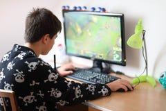 Pojke som använder den hemmastadda datoren och att spela leken Arkivfoto