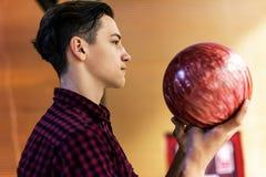 Pojke som bär bowlingklotet arkivfoto