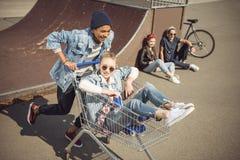 Pojke som bär den lyckliga flickan i shoppingvagn medan vänner som sitter nära ramp Arkivbild