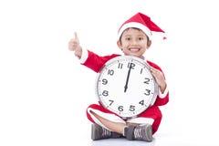 Pojke som bär den Santa Claus likformign och innehavklockan Arkivfoton