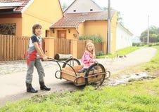 Pojke som bär en flicka på vagnen Royaltyfria Foton