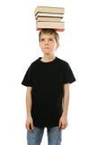 Pojke som balanserar böcker på hans huvud Arkivfoton