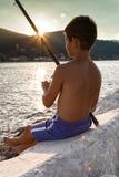 Pojke som bara fisging i solnedgången Arkivfoton