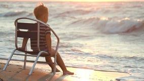 Pojke som bara sitter på stolen vid havet lager videofilmer