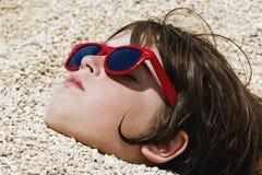 Pojke som begravas i kiselstenarna på stranden royaltyfria bilder