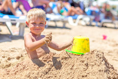 Pojke som begravas i sand på havsstranden arkivfoton