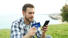 Pojke som betalar med kreditkort- och telefondet fria stock video