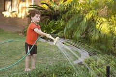 Pojke som bevattnar trädgården Arkivbilder