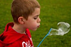 Pojke som blåser bubblor royaltyfria foton