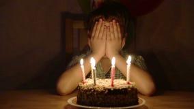 Pojke som blåser stearinljusen på födelsedagkakan lager videofilmer