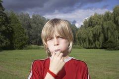 Pojke som blåser visslingen i äng arkivfoton