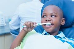 Pojke som borstar tänder i tandläkarestolen Arkivbilder