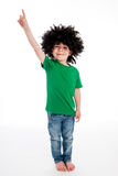Pojke som bär en stor svart peruk som pekar hans finger i luften. Arkivbild
