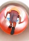 Pojke som clibming upp på en cylindrisk glidbana Arkivfoto