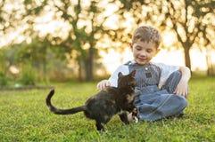 Pojke som daltar katten Arkivbilder