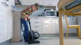 Pojke som dammsuger kökgolvet Han ordnar havreflingorna spridda på den gråa tegelplattan Slapp fokus lager videofilmer