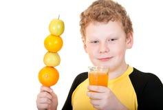Pojke som dricker ett exponeringsglas av orange fruktsaft Arkivfoto