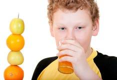 Pojke som dricker ett exponeringsglas av orange fruktsaft Royaltyfri Bild
