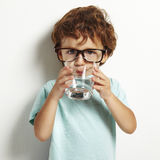 Pojke som dricker ett exponeringsglas av vatten Arkivbilder