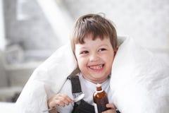 Pojke som dricker hostasirap Arkivbild