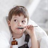 Pojke som dricker hostasirap Arkivbilder