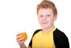 Pojke som dricker orange fruktsaft Royaltyfri Bild